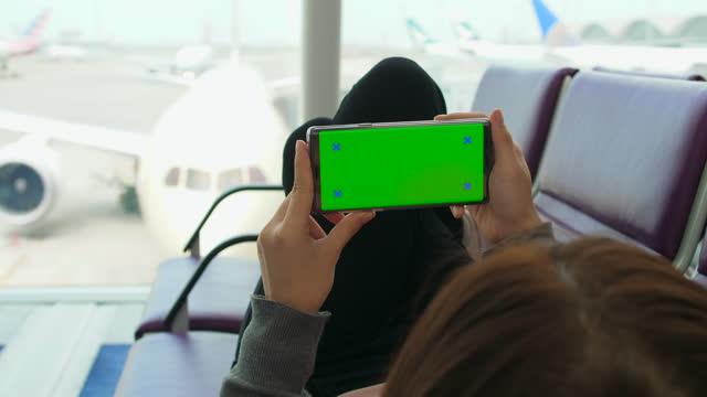 電話、グリーン画面を使用して空港出発ラウンジ - 空白の画面点の映像素材/bロール