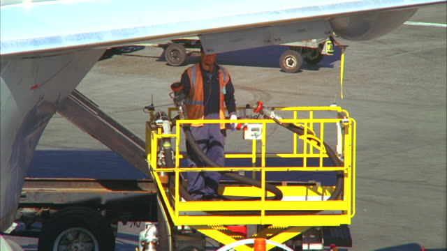 vidéos et rushes de ms, airport ground crew worker refueling aircraft then closing aircraft fuel panel, los angeles, california, usa - faire le plein d'essence
