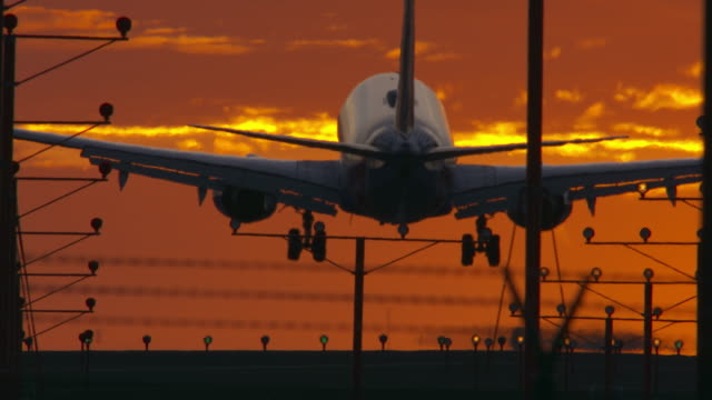 airport landing with colorful sunset sky - boeing 737 stock videos & royalty-free footage