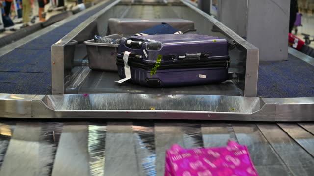 vídeos de stock e filmes b-roll de airport luggage cart stand beside  baggage on belt passenger terminal - pista de aterragem