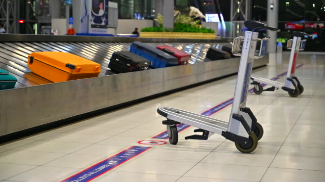 airport luggage cart stand beside  baggage on belt passenger terminal - airline check in attendant stock videos and b-roll footage