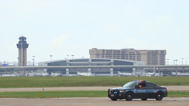 airport police vehicle foreground, airplane flies through frame background/dfw international airport, dallas-fort worth, texas, usa - dallas fort worth airport stock videos & royalty-free footage