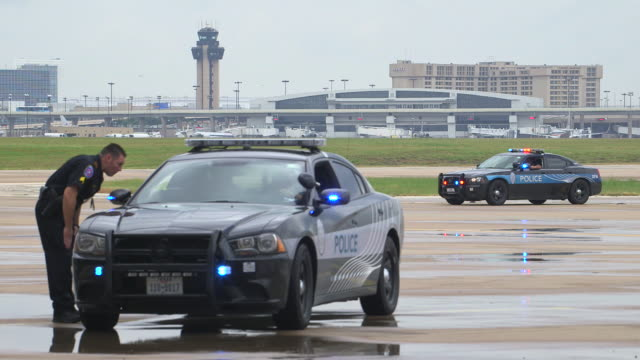 stockvideo's en b-roll-footage met airport police vehicles and officers, lights flashing with airport tower and terminal in background/dfw international airport, dallas-fort worth, texas, usa - terrorisme