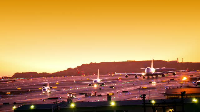 LS T/L airport runway at dusk with airliners rolling in formation  for takeoff while passenger aircraft takes off into sunset sky / Los Angeles, California, USA