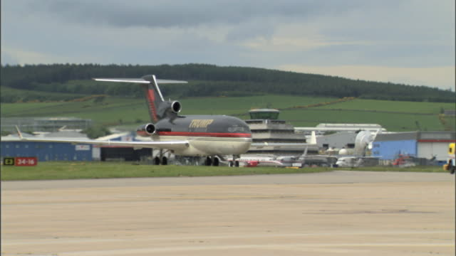 airport runway tracking donald trump's private boeing 727 trump jet taxiing on runway, turning, *tracking trump lettering on side of aircraft - aberdeen schottland stock-videos und b-roll-filmmaterial