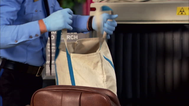 a tsa airport security guard screens luggage at bag inspection in los angeles, california. - security stock videos & royalty-free footage