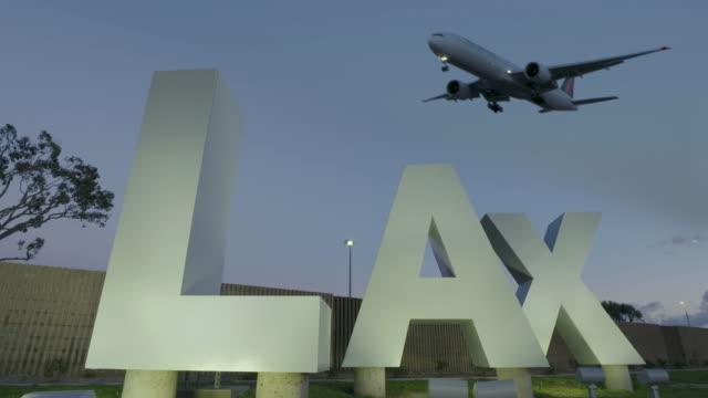 vídeos de stock e filmes b-roll de lax airport sign at twilight - aeroporto internacional de los angeles