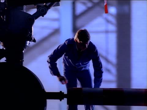 airport technicians unfasten tow bar from aircraft and attach to truck inside hangar - bar点の映像素材/bロール