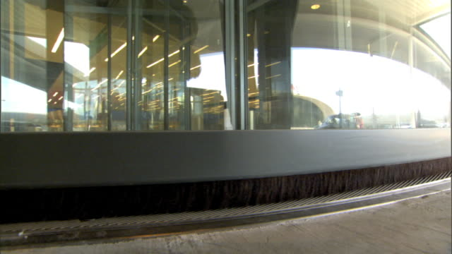 airport terminal revolving door entrance, back of unidentifiable male entering through revolving doors. nyc - kennedy airport stock videos & royalty-free footage