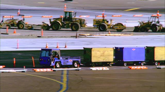 ts, ms, airport transport truck towing containers across tarmac, los angeles, california, usa - bagage bildbanksvideor och videomaterial från bakom kulisserna