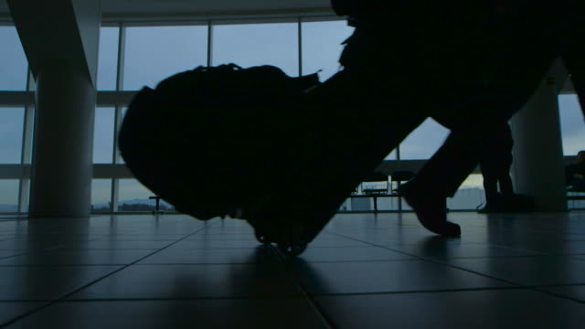 airport travel silhouette slow motion - wheeled luggage stock videos and b-roll footage