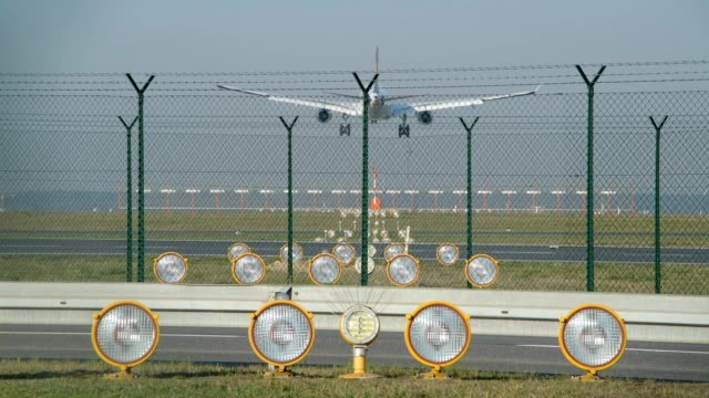 airport with supply cars and landing aircraft in front of the runway, frankfurt am main, hesse, germany - zaun stock-videos und b-roll-filmmaterial