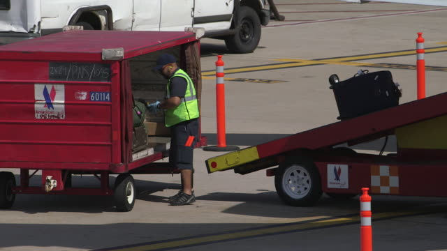 airport worker loads baggage onto commuter jet/dfw international airport, dallas-fort worth, texas, usa - dallas fort worth airport stock videos & royalty-free footage