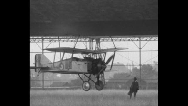 airship being towed out of hangar, people on ground / gloster grebe plane attached underneath r33 / closer shot plane / airship moving, people walk... - moving up点の映像素材/bロール