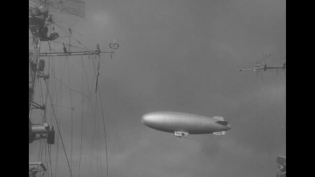 Airship cruises overhead seen between two sets of ships' rigging during Navy Day celebration