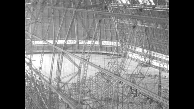airship frame under construction in hangar / cu v r jacobs giving details on craft / camera moves from side of frame towards top / model of airship... - airship stock videos & royalty-free footage