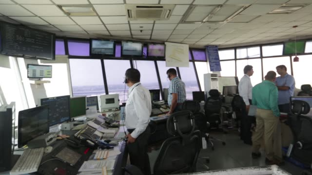 Airtraffic controllers work at a visual control room inside a control tower at Indira Gandhi International Airport in Delhi India on Monday July 18...