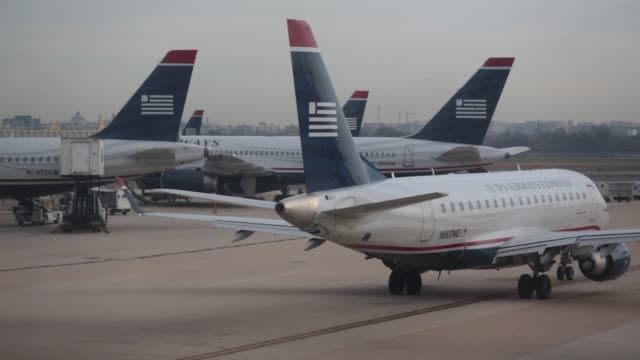 stockvideo's en b-roll-footage met us airways airplanes are towed into position on the runway at ronald reagan national airport in washington dc us airways airplanes on november 17... - us airways