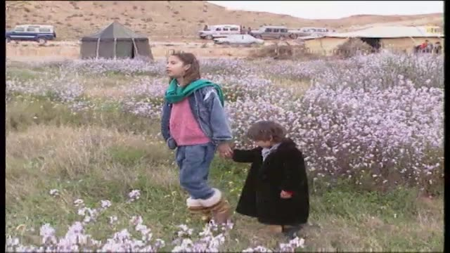 Aisha plays with her alleged younger sister Hana accompanied by other family members in a flower covered field where camels are grazing Hana Gaddafi...