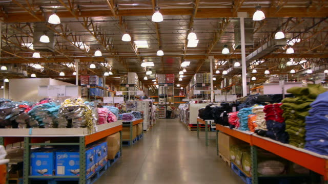 WS POV Aisle with apparel stacked on tables in big box discount store / Palm Desert, California, USA