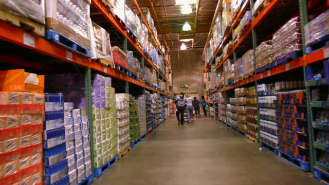 WS POV Aisle with floor to ceiling shelves stacked with household supply items in big box discount store / Palm Desert, California, USA