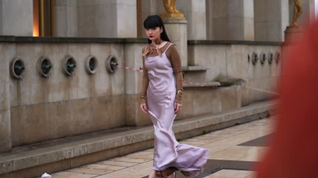 akimoto kozue wears a pale purple mauve flowing silky dress, a brown top, a necklace with leaf-shaped features, golden bracelets, outside ann... - dress stock videos & royalty-free footage
