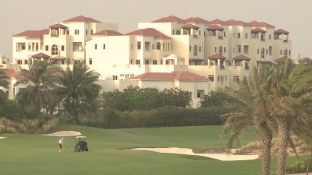 al badia golf club, dubai. medium long shot of a golfer teeing off at the al badia golf club in festival city. - golf swing stock videos & royalty-free footage