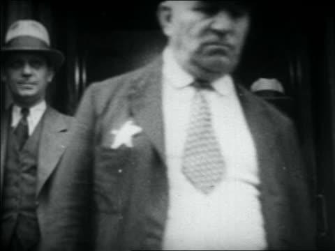 vidéos et rushes de al capone following man wearing badge exiting building - 1931
