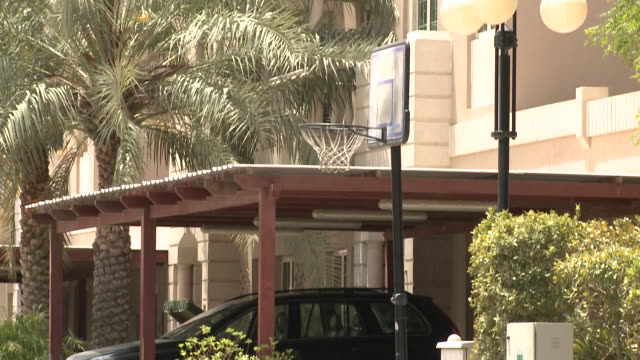 al garhoud residential district, deira. tilt-down on a basketball pole in front of a villa in a quiet residential street in garhoud as an asian... - domestic life stock videos & royalty-free footage