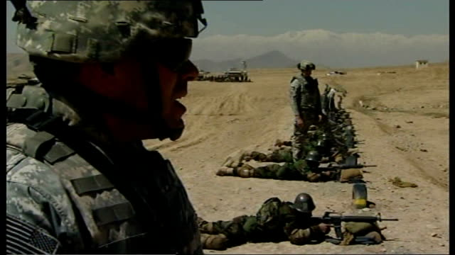 al qaida terrorists switch focus from iraq afghanistan near kabul ext various shots of new afghan army recruits lying on ground firing guns at... - military training stock videos & royalty-free footage
