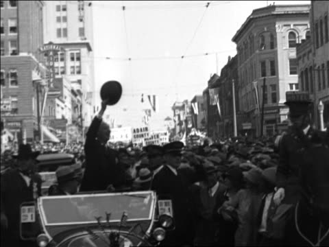 vidéos et rushes de al smith standing in car in parade waving hat / documentary - 1928