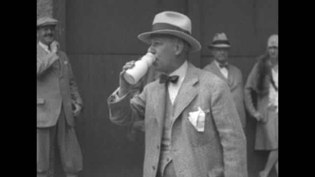 stockvideo's en b-roll-footage met al smith wearing a three piece suit bow tie and straw hat and a holding bottle in hand examines a calf / ms smith drinking from milk bottle three... - al smith