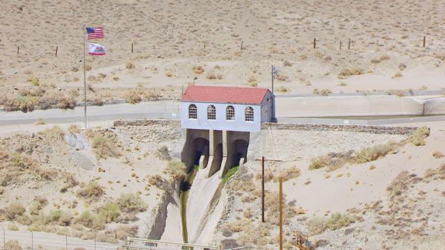 vídeos y material grabado en eventos de stock de ws aerial pov alabama gatehouse and flag pole along los angeles aqueduct in owens valley desert / california, united states  - aqueduct