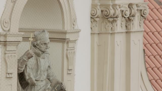 stockvideo's en b-roll-footage met ha alabaster statue of religious figure in arched niche of ornate building facade near scrolled columns - breedbeeldformaat