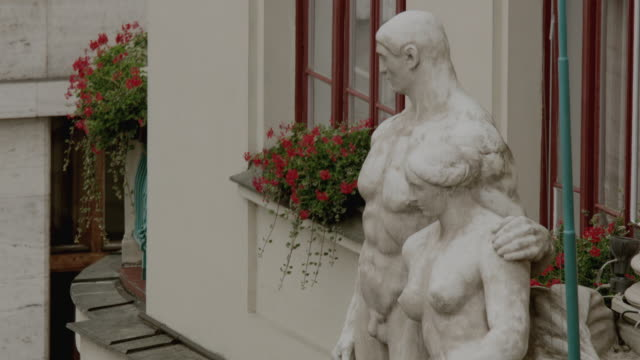 ha alabaster statues of a man and woman outside a stone building with red flowers in a window box and red window frames - window box stock videos & royalty-free footage