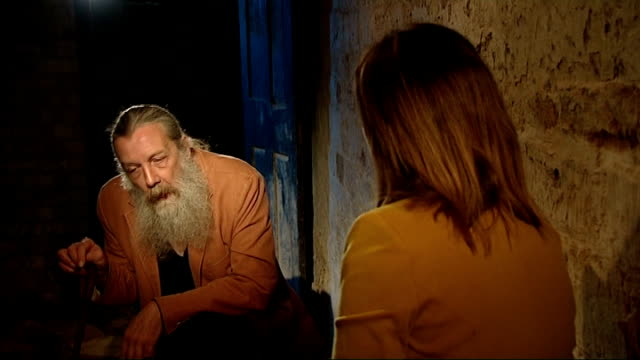 alan moore interview; long shot moore talking to reporter in crypt before door slams shut hiding them from view / various cutaways of alan moore... - stool stock videos & royalty-free footage
