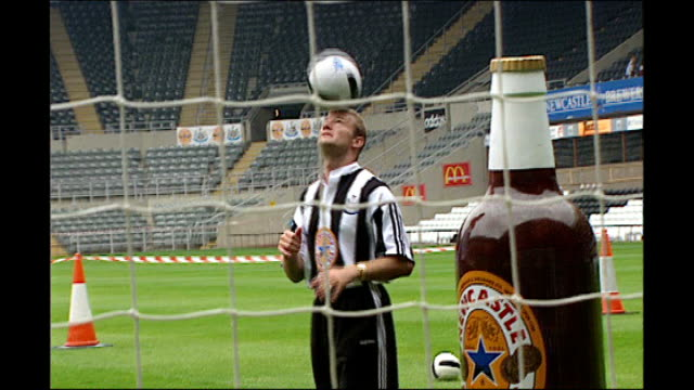 Alan Shearer signs for Newcaste United Gates of St James' Park / Shearer knocking dwon cut outs of Newcastle Brown Ale bottles standing in goalmouth...