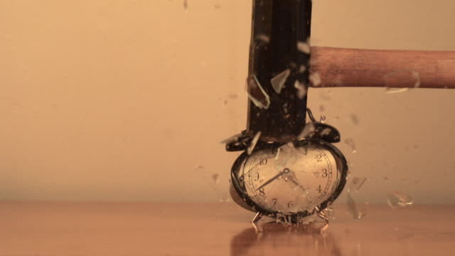 Alarm clock is smashed by sledge hammer (slow motion)