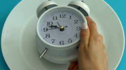 Alarm clock on empty plate, healthy diet schedule, daily nutrition, closeup