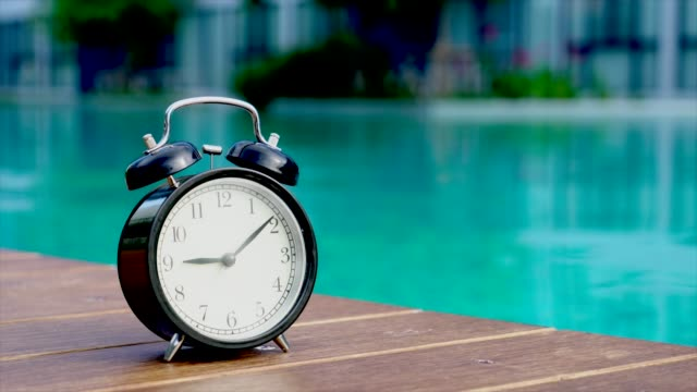 alarm clock on wooden board with green bokeh background - yard measurement stock videos and b-roll footage
