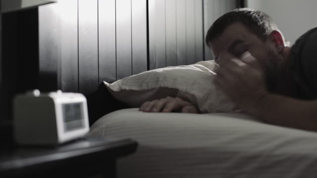 Alarm clock startles sleeping man, gets out of bed