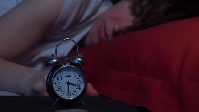 女性の目を覚ます目覚まし時計 - 目覚まし時計点の映像素材/bロール