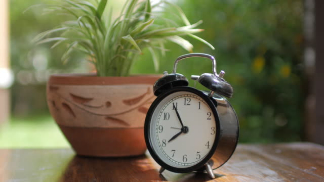Alarm Clock with green plant on wooden table with green bokeh background , dolly shot right to left
