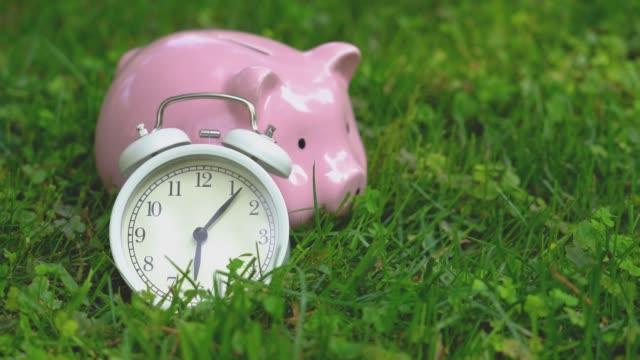 vídeos de stock, filmes e b-roll de despertador com banco piggy e alarme de toque no gramado - equilíbrio vida trabalho