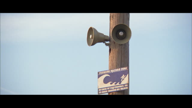 ZI Alarm horns mounted on telephone pole, with sign reading TSUNAMI HAZARD ZONE and a graphic of a running figure chased by a massive wave