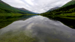 Alaska 4k drone footage of tracking over a glassy calm lake toward rustic mountains as the vehicles and trucks drive on the scenic Alaska highway on the right.  Trucks and cars on Alaska transportation system