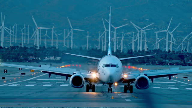 ls alaska air jetliner taxis towards camera at dusk against background of renewable energy producing wind farm in far distance - air vehicle stock-videos und b-roll-filmmaterial