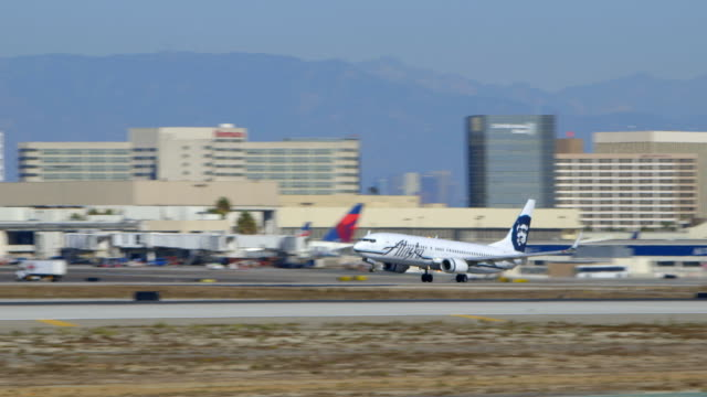 alaska airlines boeing-737 takes off from lax, daytime - boeing 737 stock-videos und b-roll-filmmaterial