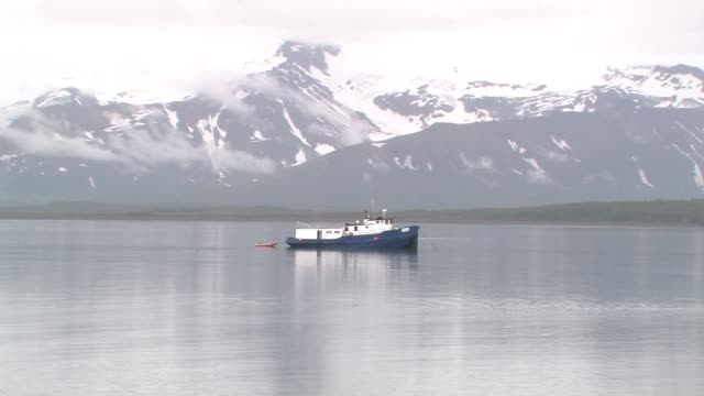 vídeos y material grabado en eventos de stock de ws, usa, alaska, katmai national park, boat anchored in bay, snow capped mountains in background - anclado