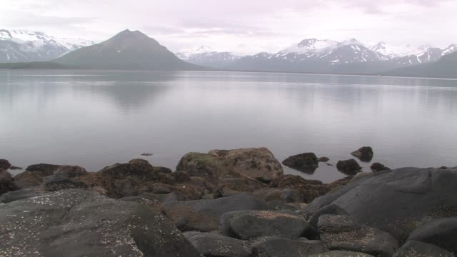 ws, pan, usa, alaska, katmai national park, boat anchored in bay, snow capped mountains in background - anchored stock videos & royalty-free footage